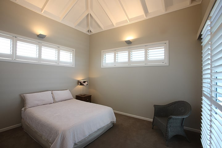White interior plantation shutters in bedroom