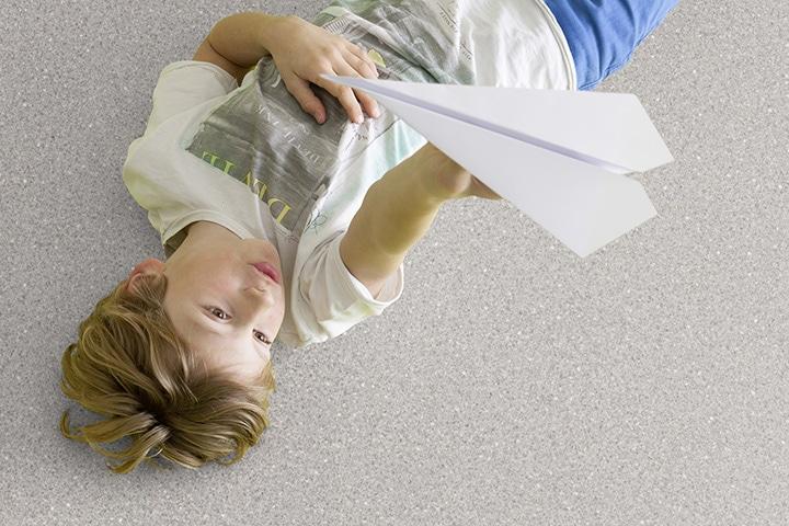 Boy lying on vinyl flooring