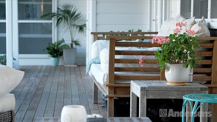 Wooden outdoor bench and flowers in a pot