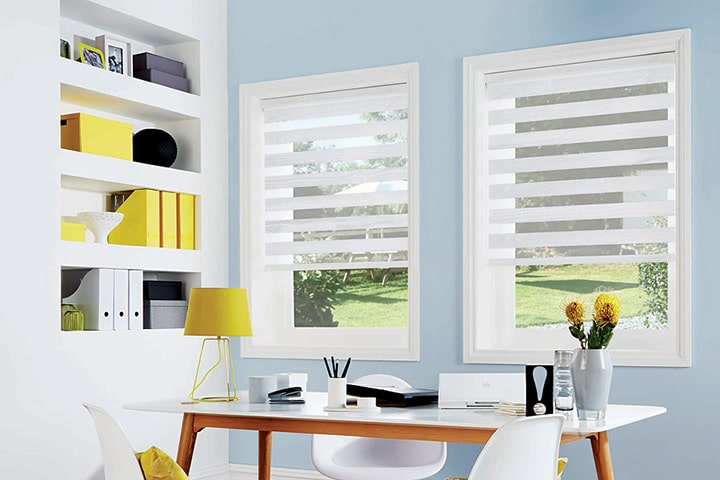 Home office with two windows covered by sheer blinds