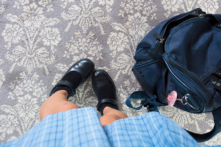 School girl's shoes on traditional patterned carpet