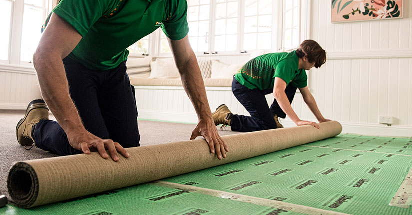 Two Andersens installers roll out a new carpet in a home